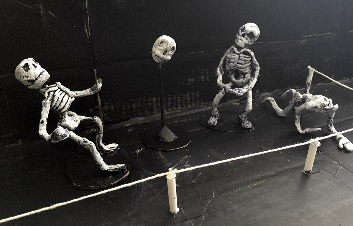 Three skeletons, sculpted out of clay and placed in our scale model