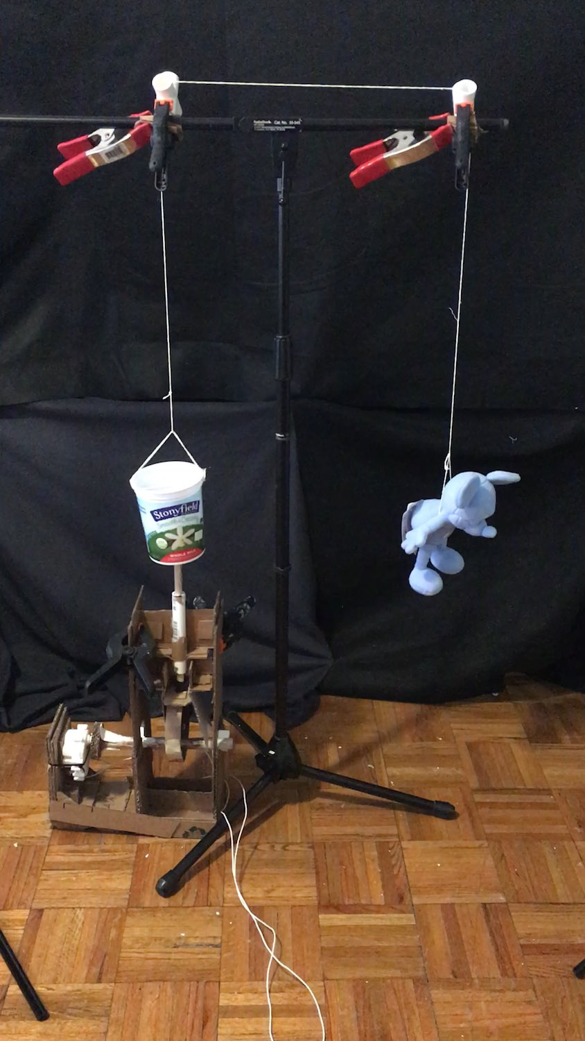 A stuffed Mickey Mouse hanging from a string, attached to a cam mechanism